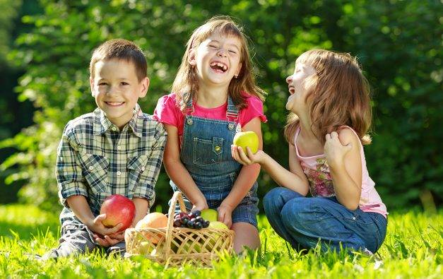 Three kids picking apples and other fruit