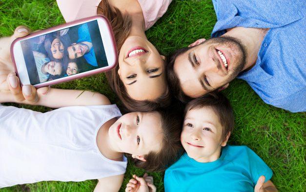 Happy family lying on grass having their photo taken
